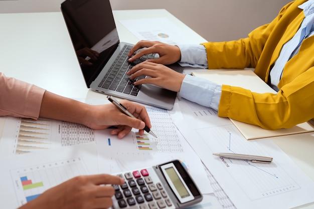 Księgowy wskazując na laptopie na spotkanie zespołu w pokoju biurowym. koncepcja finansów i rachunkowości