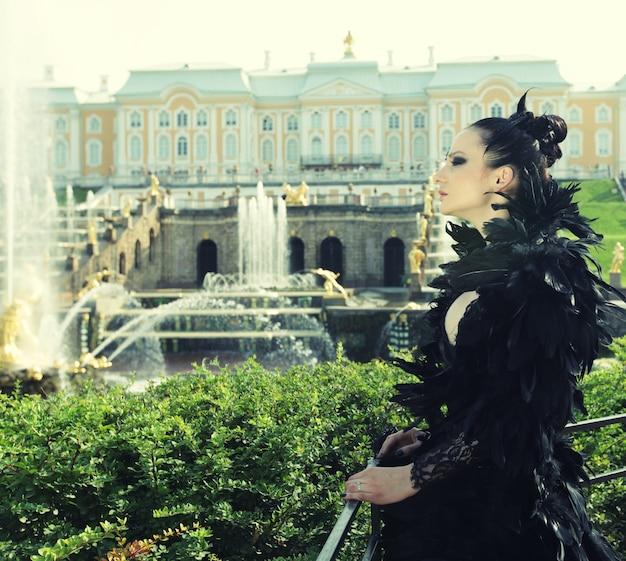 Księżniczka w parku obok fontanny i pałacu