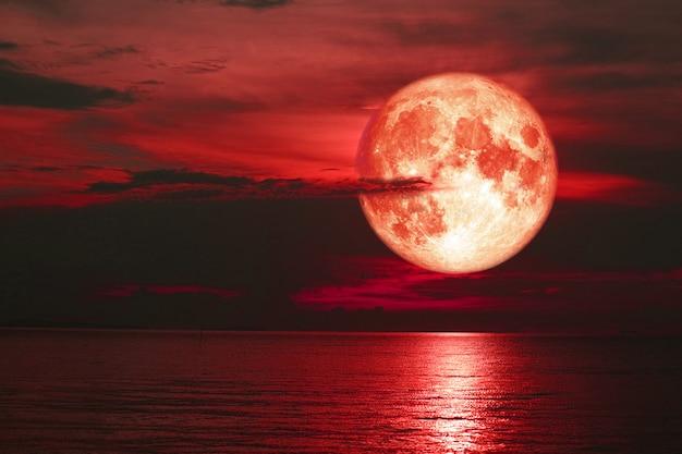 Księżyc czerwony jesiotra z powrotem na chmury sylwetka na niebie słońca
