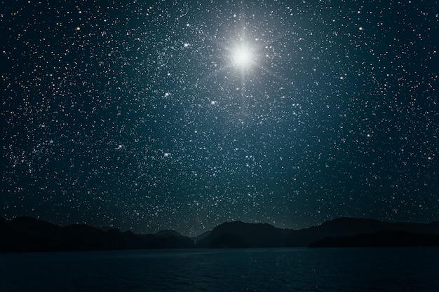 Księżyc na tle jasnego nocnego gwiaździstego nieba odbijającego się w morzu.