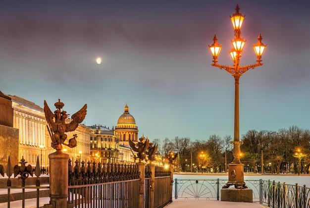 Księżyc nad katedrą św. izaaka i latarnią na placu pałacowym w zimowy poranek w sankt petersburgu