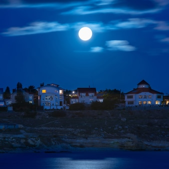 Księżyc nad rzeką przez miasto z błękitnym niebem i chmurami
