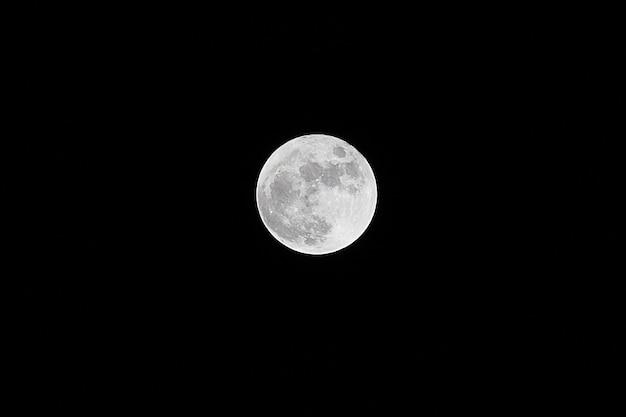 Księżyc w pełni nad ciemnym czarnym niebem w nocy