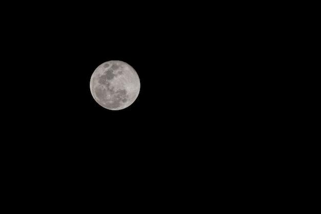 Księżyc w pełni z fotografią brzoskwiniowego czarnego nieba w tle zrobioną aparatem dsrl i teleobiektywem