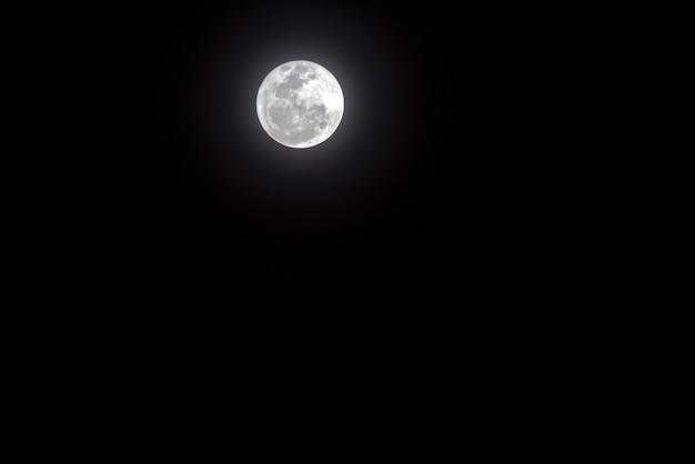 Księżyc w pełni z jasną aureolą na ciemnym niebie