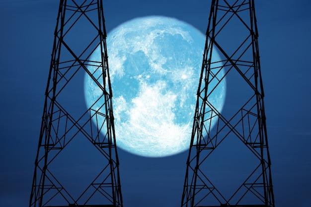 Księżyc w pełni zbiorów na niebie i sylwetka zasilania słup elektryczny