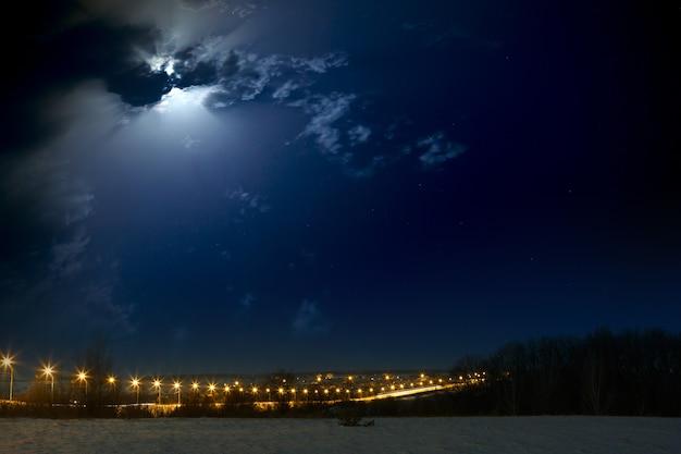 Księżyc z chmurami na nocnym niebie. autostrady samochodowe oświetlone latarnie. krajobraz sfotografowany zimą