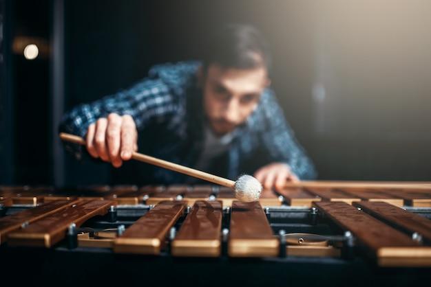 Ksylofon z patykami w dłoniach, muzyk w akcji, drewniane dźwięki. muzyczny instrument perkusyjny, wibrafon
