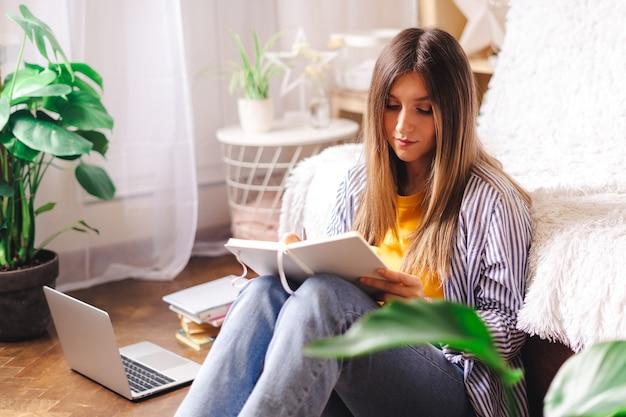 Kształcenie na odległość, edukacja i praca online. biznes kobieta pisze w zeszycie, siedząc na podłodze. szczęśliwa i uśmiechnięta dziewczyna z laptopem w domowym biurze. korzystanie ze sklepów komputerowych i internetowych.