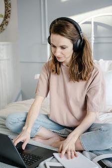 Kształcenie na odległość, edukacja i praca online. szczęśliwa kobieta na co dzień ze słuchawkami, pracująca na laptopie zdalnie z domu na łóżku.