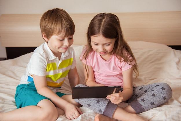 Kształcenie na odległość edukacja online. dzieci siedzą z tabletem na łóżku w pokoju. dzieci z gadżetem. kwarantanna i samoizolacja