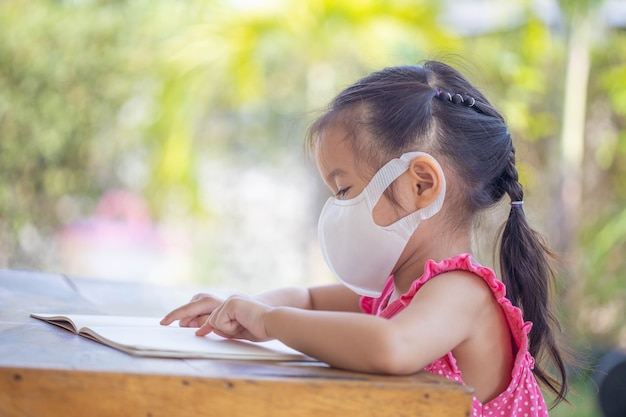 Kształcenie na odległość edukacja online. dziecko w masce, aby obejrzeć lekcję online.