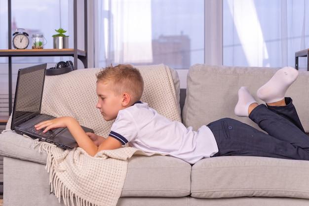 Kształcenie na odległość edukacja online uczeń chłopiec uczy się w domu i odrabia lekcje w szkole dom