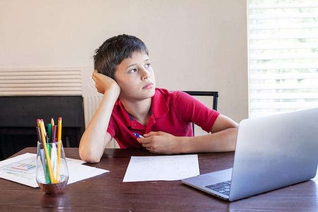 Kształcenie na odległość edukacja online. uczeń uczy się w domu i odrabia lekcje w szkole. jest znudzony i zmęczony.