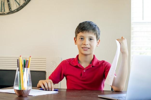 Kształcenie na odległość edukacja online. uczeń uczy się w domu i odrabia lekcje w szkole.