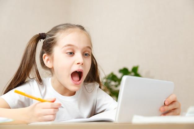Kształcenie na odległość edukacja online. uczennica uczy się w domu z notatnikiem i odrabia lekcje w szkole. dziewczyna odrabia lekcje z radością i zainteresowaniem. komunikacja dystansu społecznego podczas kwarantanny