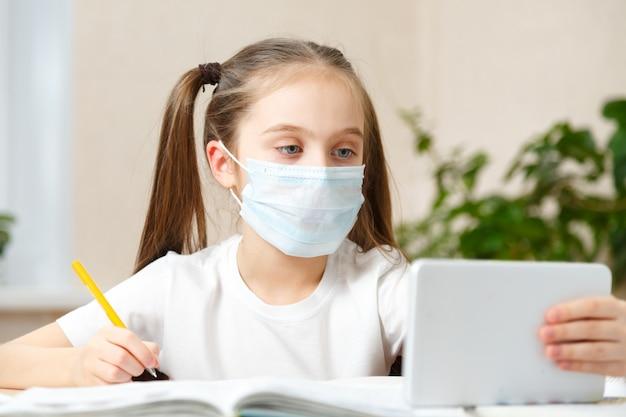 Kształcenie na odległość edukacja online. uczennica uczy się w domu z notebookiem laptopa cyfrowego tabletu i odrabia lekcje w szkole.