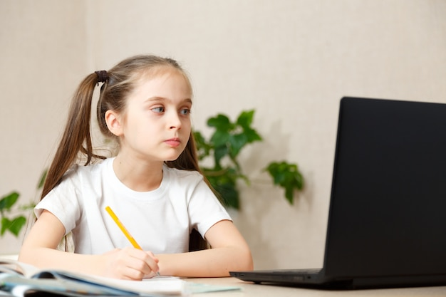 Kształcenie na odległość edukacja online. uczennica uczy się w domu