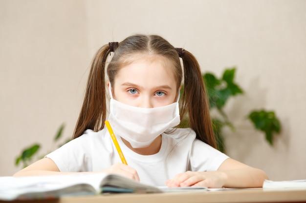 Kształcenie na odległość edukacja online. uczennica w masce medycznej ucząca się w domu,