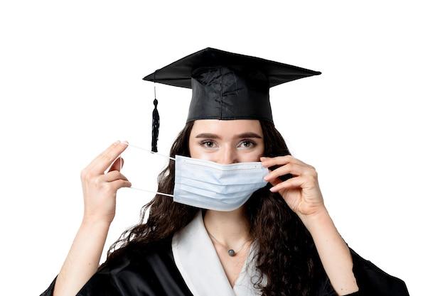 Kształcenie na odległość online z maską medyczną w okresie koronawirusa covid-19. uczyć się w domu. ukończenie college'u. absolwent w czarnej szacie uśmiechnięty. ukończ uniwersytet i uzyskaj tytuł magistra