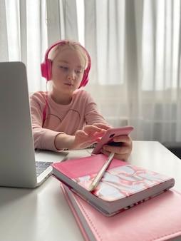 Kształcenie na odległość. uczennica w różowych słuchawkach studiująca pracę domową podczas lekcji online w domu przez internet. dystans społeczny podczas kwarantanny
