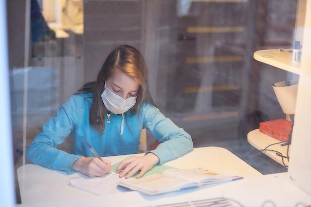 Kształcenie na odległość w kwarantannie, nastolatka w masce medycznej, która robi lekcje