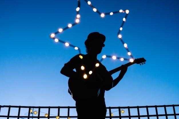 Kształt człowieka grającego na gitarze podczas koncertu na żywo w nocy. festiwal muzyki akustycznej podczas wiosennych i letnich nocy. gwiazdy muzyki wykonującej z gitarą o zachodzie słońca.