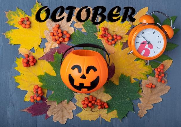 Kształt dyni z przerażającym uśmiechem jack o lantern, pomarańczowym budzikiem i napisem październik na tle suszonych liści, jagody jarzębiny na szarym tle. koncepcja czasu wakacji na halloween