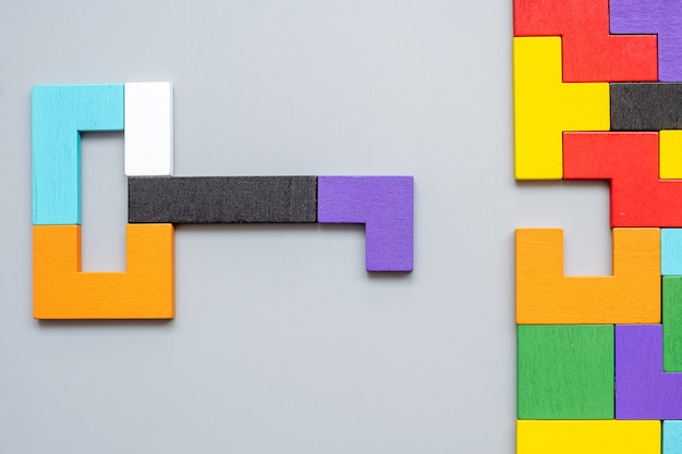 Kształt klucza i dziurki od klucza z geometrycznych kolorowych drewnianych puzzli.