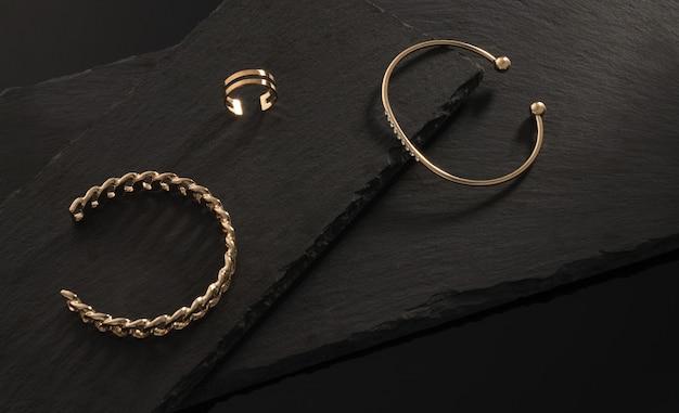 Kształt łańcuszka i złote bransoletki z brylantami i pierścionek na ciemnych kamiennych płytach z miejscem na kopię