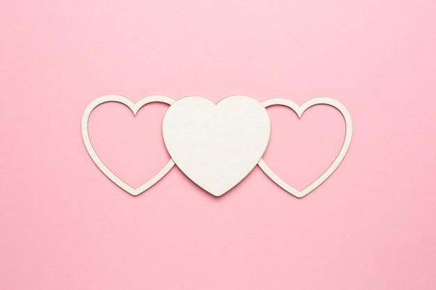 Kształt serca na pastelowym różowym tle. koncepcja karty walentynkowej. widok z góry, miejsce na tekst