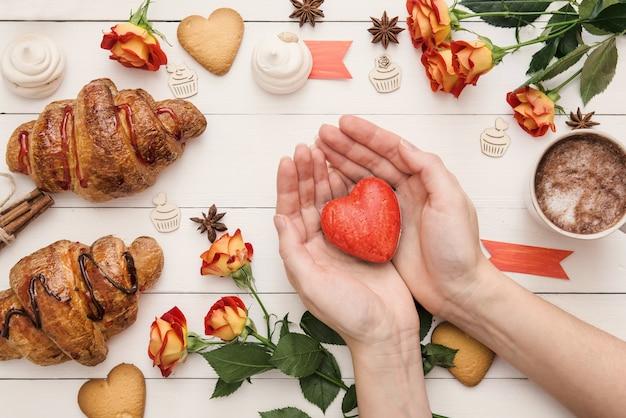 Kształt serca na rękach nad walentynkowym dekorowanym stołem, świeżo upieczonymi rogalikami i kwiatami