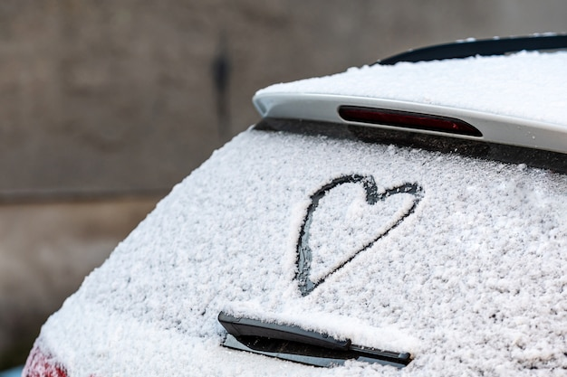 Kształt serca na tylnym oknie samochodu pokryte śniegiem