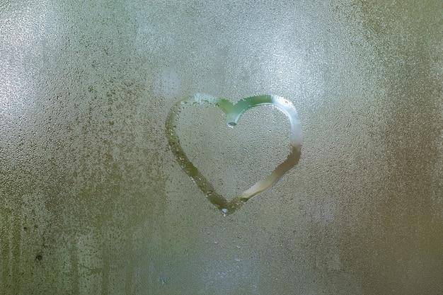 Kształt serca narysowany na mokrym oknie w deszczowy dzień