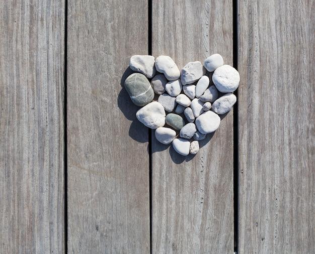 Kształt serca wykonane z kamieni na drewnianych deskach molo w tle love zen life concept