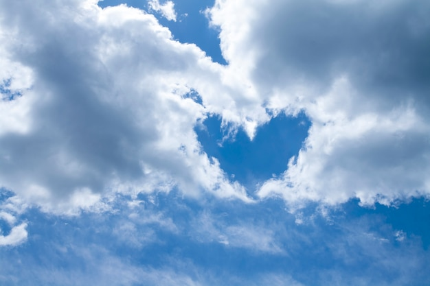 Kształt serca wykonany z biało-szarych chmur na niebieskim niebie