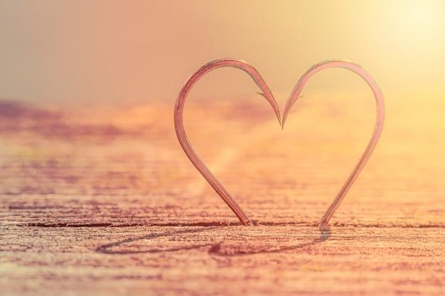 Kształt serca wykonany z dwóch haczyków rybnych z cieniami.