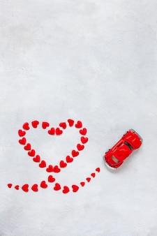 Kształt serca wykonany z małych czerwonych serc i czerwonego samochodzika