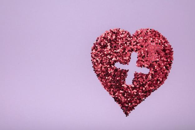 Kształt serca z czerwonym brokatem na różowym tle z medycznym krzyżem. koncepcja miłości.