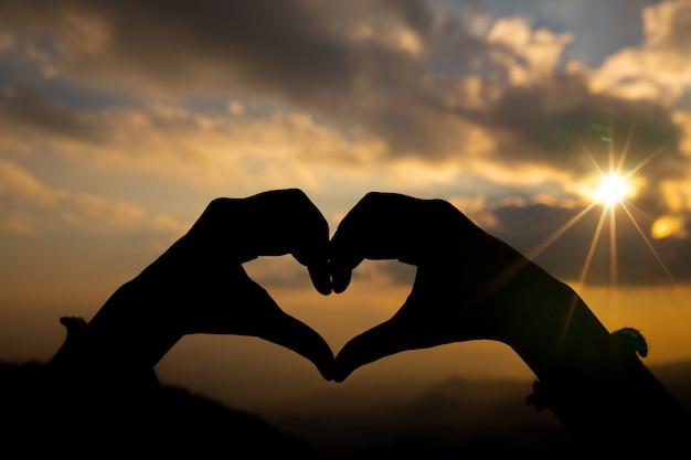 Kształt serca z dwóch rąk z tłem wschód słońca.