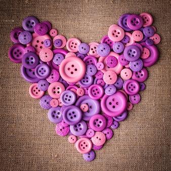 Kształt serca z guzików na tkaninie płóciennej
