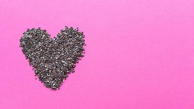 Kształt serca z nasion chia na różowym tle. proste mieszkanie o pastelowej fakturze.