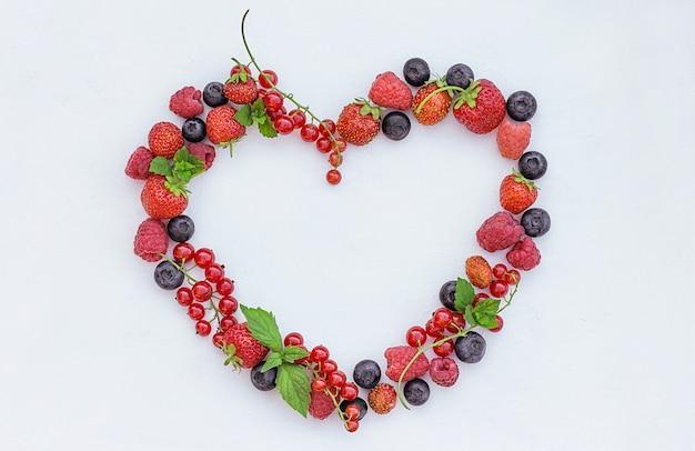 Kształt serca z różnych świeżych jagód na jasnym tle
