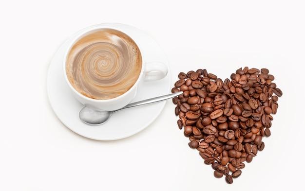 Kształt serca z ziaren kawy z filiżanką kawy na białym tle