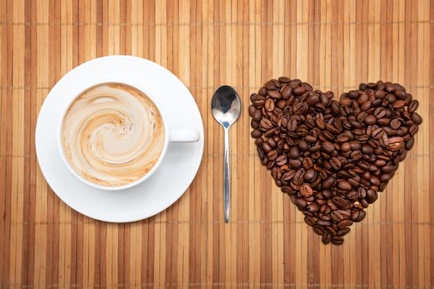 Kształt serca z ziaren kawy z filiżanką kawy na brązowym tle