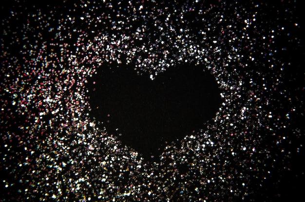 Kształt serca ze srebra błyszczy na czarnym tle, szczęśliwych walentynek, dnia matki, leżał płasko, widok z góry