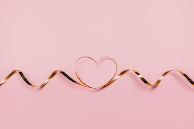 Kształt serca złotą wstążką na na białym tle różowym