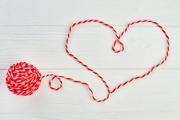 Kształt serduszka z czerwonej wełnianej nici. serce z czerwonej wełnianej przędzy na białym tle drewnianych. wełniana piłka do dziania na podłoże drewniane. szczęśliwych walentynek.
