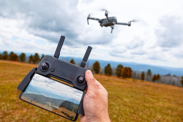 Kształtowanie krajobrazu na dronie. młody człowiek trzyma w ręku kwadrokopterowy panel kontrolny z monitorem i obrazem gór