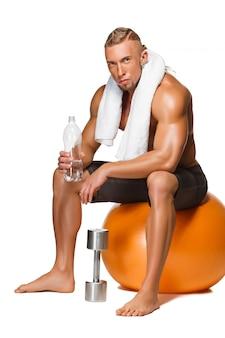 Kształtujący i zdrowy ciało mężczyzna siedzi na sprawności fizycznej piłce